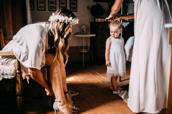 Bride puts on her shoes witnessed by little child