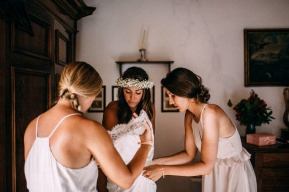 Brides maids help bride with the wedding gown