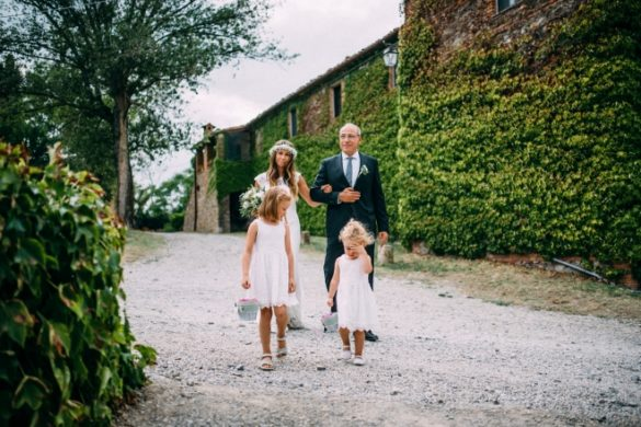 Father of the bride brings his daughter to ceremony with 2 bridesmaids