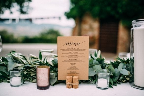 Detail of wedding table with candles, menu and eucalyptus garland