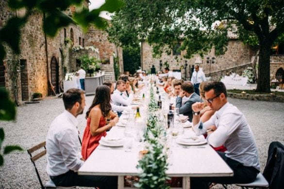 Guests at wedding dinner table courtyard Tuscan borgo