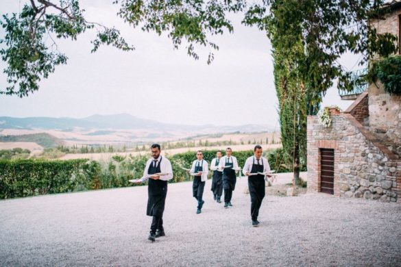 Waiters serve food at borgo with courtyard with panoramic view of Val d'Orcia