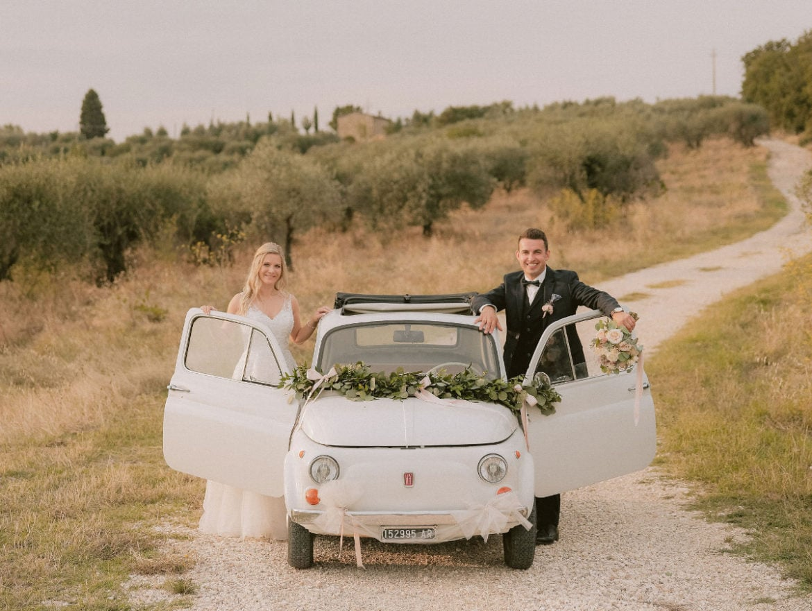 German wedding couple with vintage Fiat 500 in olive grove in Tuscany