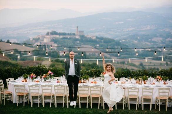 Bruid en bruidegom voor dinertafel buiten in de Toscaanse heuvels