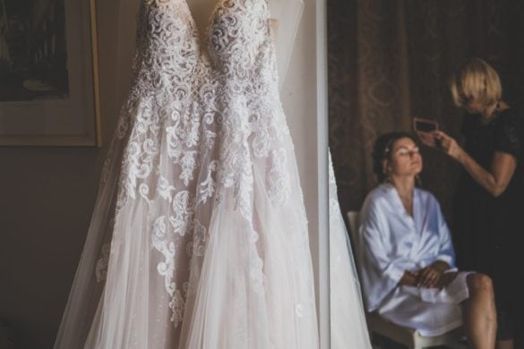 Detail of wedding dress and make up artist while bride is getting ready.