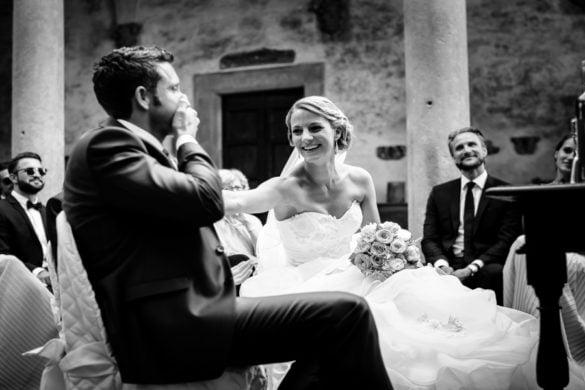 Lächelnde Braut mit ihrem Mann bei ihrer Hochzeitszeremonie im Hof eines Schlosses in der Toskana