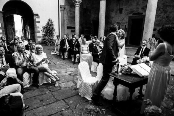 Neuvermählte küssen sich am Ende der Zeremonie im Innenhof eines Schlosses