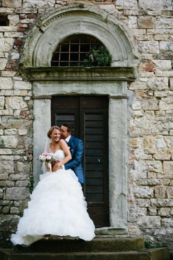 Porträt von Frischvermählten mit rosa Brautstrauß auf den Stufen eines Schlosses
