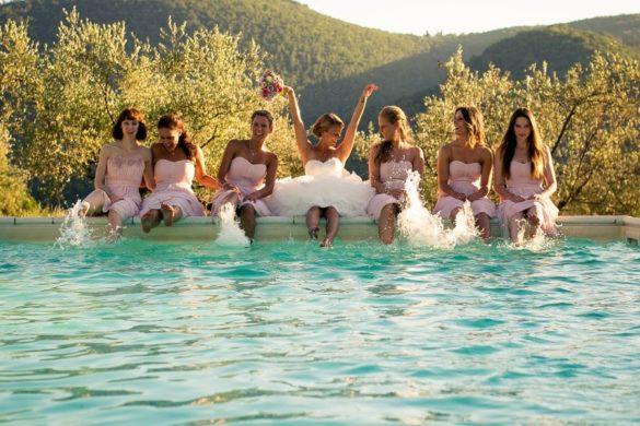 Lustiges Hochzeitsfoto der Braut und der Brautjungfern am Pool einer privaten Villa in der Toskana