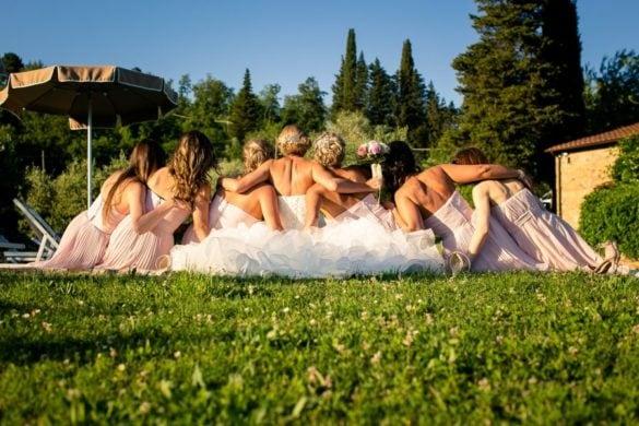 Lustiges Hochzeitsporträt einer Braut und ihrer Brautjungfern in den Hügeln der Toskana