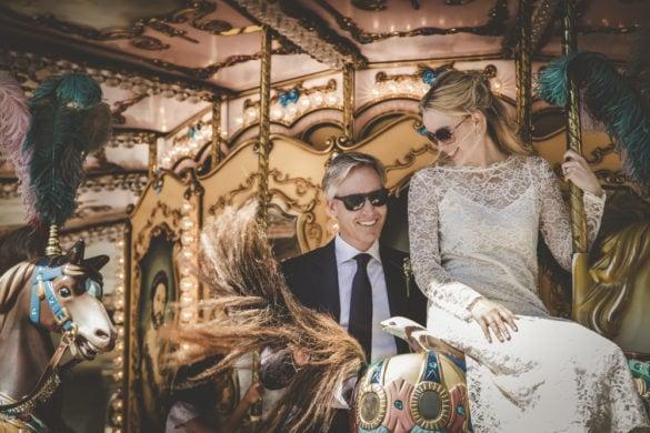 Joyful photo of wedding couple having fun in carousel
