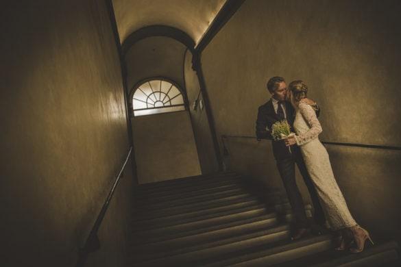 Groom kisses bride on steps of Palazzo Vecchio