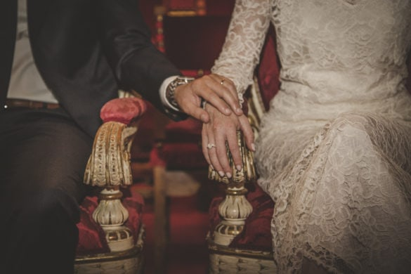Groom touches his wife's hand after wedding ring exchange