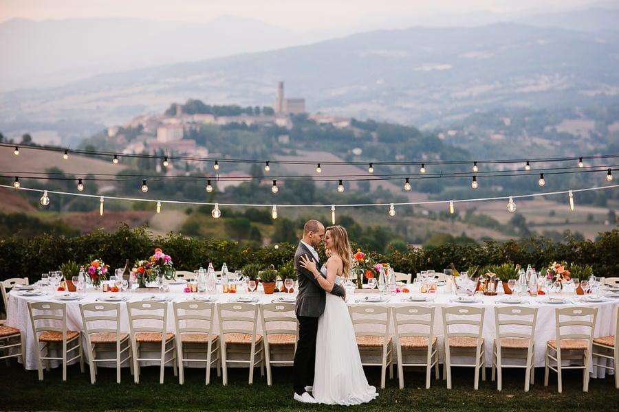 wunderschöner Hochzeitstisch in der Toskana mit Panoramablick und Partylichtern.