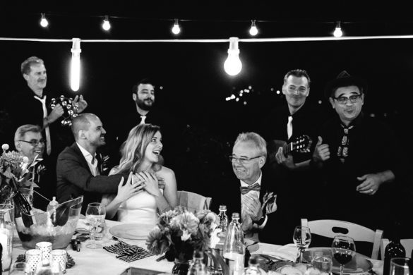 Musiker singen für Ehepartner während des Hochzeitsessens im Freien in der Toskana