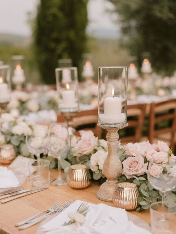 Elegant wedding dinner decoration with candle holders and blush colored flower garland.