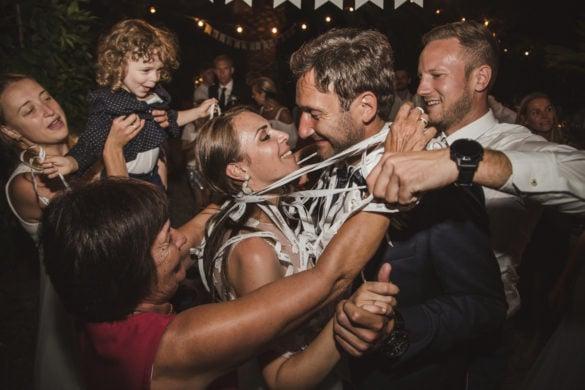 Braut und Bräutigam werden von den Hochzeitsgästen dekoriert.