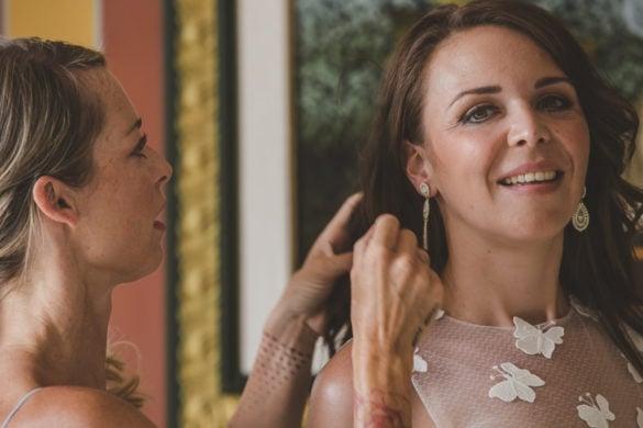 Brautjungfer hilft der Braut mit Ohrringen