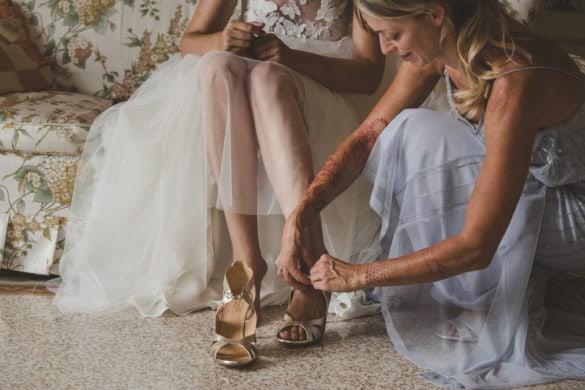 Brautjungfer hilft der Braut mit Brautschuhen.