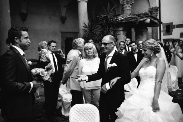 Ankunft der Braut und ihres Vaters bei einer symbolischen Zeremonie unter freiem Himmel in einer mittelalterlichen Burg in der Toskana