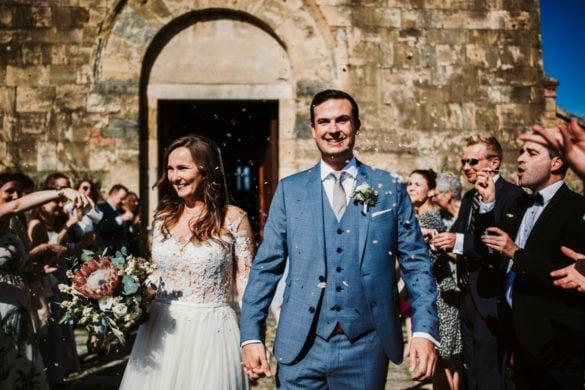 Braut und Bräutigam verlassen die Santa Maria Assunta Kirche auf dem Platz von Monteriggioni.