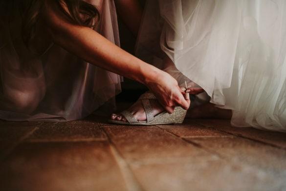 Assistentin Braut hilft beim Anziehen von Brautschuhen