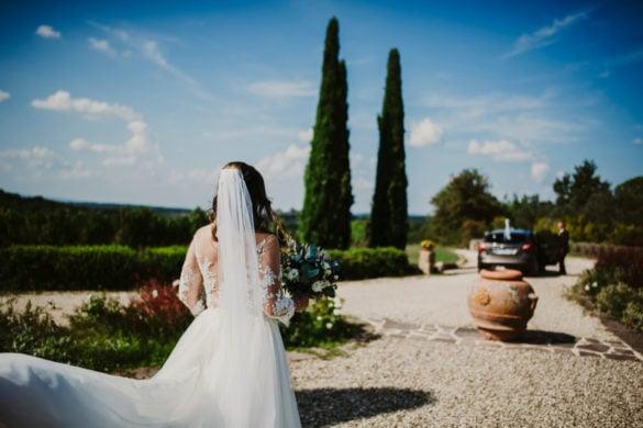 Abfahrt der Braut zur toskanischen Zeremonie mit Hochzeitsauto und Zypressen im Hintergrund